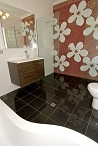 Red and White flower mosaic wall, along with black floor, frameless glass shower screen, and curved bath